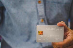 mão de homem segurando cartão de crédito
