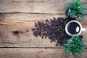 caneca de café e grãos de café na mesa foto