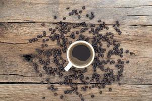 caneca de café e grãos de café na mesa, vista superior foto