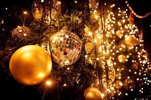 árvore de natal com bola dourada e fundo de luzes bokeh