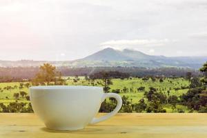 xícara de café com uma montanha ao fundo