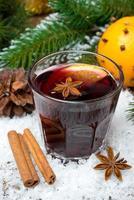 vinho quente com especiarias no copo, vertical foto