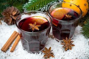 vinho quente com especiarias em taças na neve foto