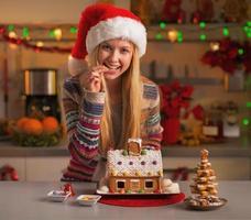 adolescente feliz com chapéu de Papai Noel com casa de biscoitos de natal