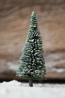cartão de natal - uma árvore de natal em miniatura na neve foto