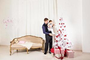 menina brincando com o pai perto da árvore de natal foto