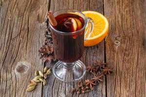 vinho quente e especiarias na mesa de madeira envelhecida