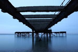 antigo cais abandonado com longa exposição de mar