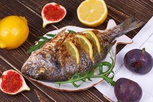dourado de peixe grelhado inteiro servido com limão e figos; foto