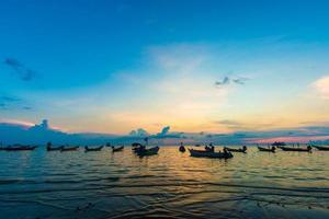 pôr do sol no mar da ilha de tao com barco foto