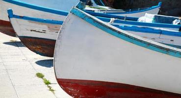 velhos barcos de pesca de madeira estão pousados na costa do mar