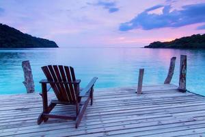 cadeira de madeira única no porto sobre o mar ao entardecer
