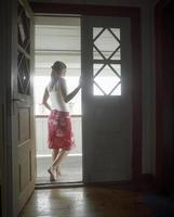 mulher em pé na porta aberta