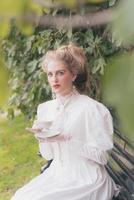 mulher vitoriana elegante tomando uma xícara de chá no assento do jardim.