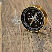 bússola magnética de ouro na placa de madeira