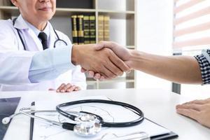 médico apertando a mão do paciente foto