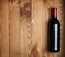 garrafa de vinho tinto no fundo da mesa de madeira