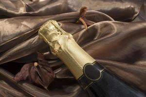 champanhe e flores secas em um fundo de seda