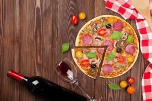 pizza italiana com calabresa, tomate, azeitonas, manjericão e wi vermelho