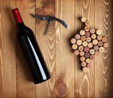 garrafa de vinho tinto, saca-rolhas e rolhas em forma de uva
