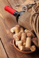 garrafa de vinho tinto, rolhas e saca-rolhas sobre fundo de mesa de madeira