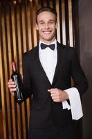 garçom bonito segurando uma garrafa de vinho tinto e uma toalha
