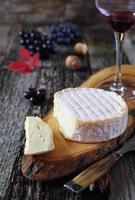 uvas, queijo francês e taça de vinho