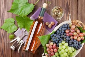 cacho de uvas, vinho branco e saca-rolhas