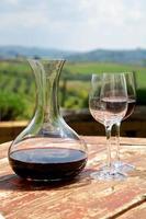 vinho tinto em uma garrafa de vinho e duas taças de vinho em um antigo vinhedo