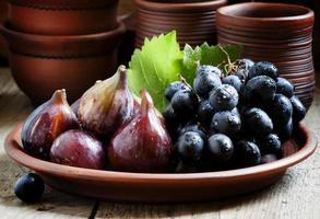 figos e uvas maduros em um prato de barro foto