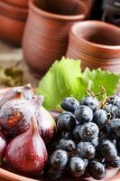 figos e uvas maduros em um prato de barro