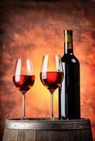 garrafa e dois copos de vinho tinto em barril de madeira