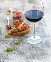 conjunto de aperitivo de vinho. copo de vinho tinto, brushettas com fresco