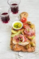 torrada com presunto, azeitonas e tomate cereja no tabuleiro
