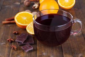 Vinho quente com laranja e especiarias em fundo de madeira foto