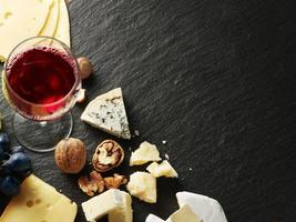 diferentes tipos de queijos com taça de vinho e frutas.