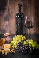 diferentes tipos de uva com garrafa de vinho foto