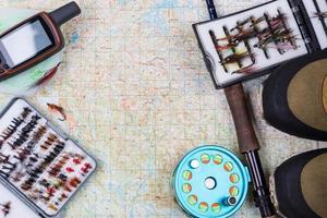 equipamento de pesca e sapatos no mapa de papel foto