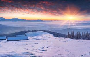 nascer do sol de inverno colorido nas montanhas nevadas. foto