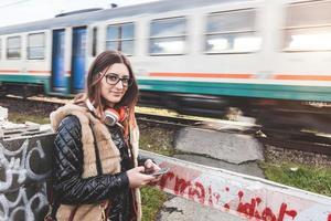 garota digitando no telefone inteligente com trem passando no fundo.