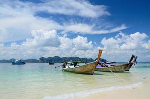 grupo de barco de cauda longa na praia com ilha