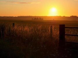 vista do monumento pré-histórico de stonehenge com o nascer do sol de verão