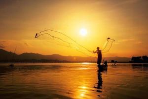 jogando rede de pesca durante o pôr do sol foto