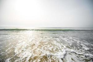ondas de espuma na praia foto