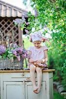 menina criança fazendo coroa de flores lilás no jardim ensolarado de primavera foto