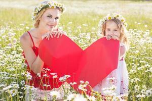 mãe e filho estão segurando um coração vermelho
