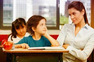 professor e aluno olhando um para o outro na sala de aula primária