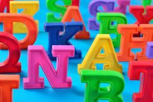 letras do alfabeto coloridas de plástico fechadas em um azul foto