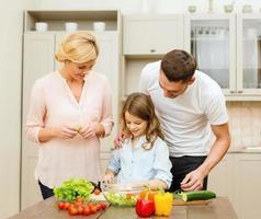 família feliz cozinhando o jantar na cozinha de casa foto