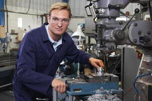 retrato do engenheiro usando furadeira na fábrica foto